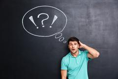 Puzzled confuzed young man over chalkboard background - stock photo