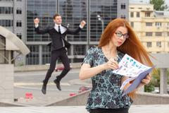 Red-haired businesswoman and businessman on background - stock photo