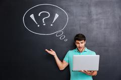 Surprised attractive young man using laptop over blackboard background - stock photo