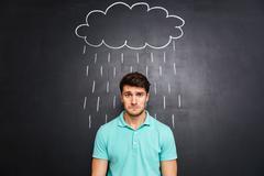 Sad man standing under the rain drawn on blackboard background - stock photo