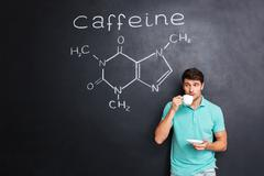 Man drinking coffee over blackboard with structure of caffeine molecule Stock Photos