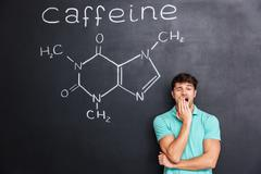 Exhausted fatigued man yawning over chalkboard with drawn caffeine molecule Stock Photos