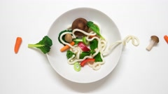 Vegetables and udon noodles becoming a soup.Stop motion animation. 4K resolution Stock Footage