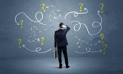 Unsure businessman with question marks - stock photo