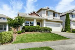 House exterior with curb appeal. View of entrance porch, garage and driveway. - stock photo