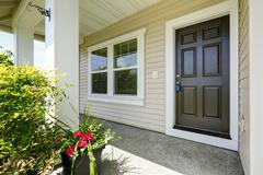Open porch with concrete floor, column and entrance brown door. Decorated wit Stock Photos