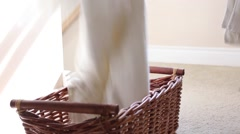 Towels dropped into laundry basket Stock Footage