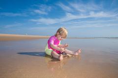Baby counting sea shells Stock Photos