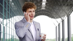 Young successful businessman speaking on phone, business centre background Stock Footage