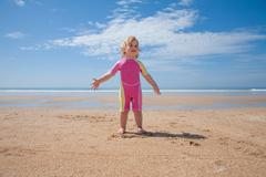 Baby swimsuit standing at beach Stock Photos