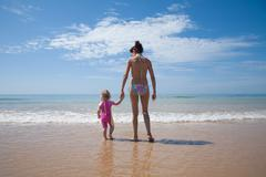 Back mother and baby at ocean Stock Photos