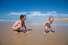 Funny baby playing at shore with mother Stock Photos
