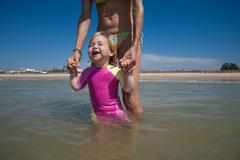 Happy baby with mom at ocean Stock Photos