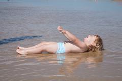 Lying laughing baby at seaside Stock Photos