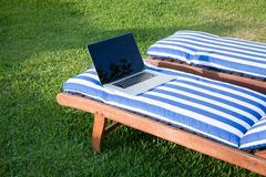 Open laptop on mat deckchair Stock Photos