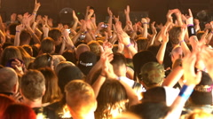 A lot of fans applauding and waving their hands at a rock concert. Slow motion. - stock footage