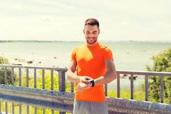 smiling young man with smart wristwatch at seaside - stock photo