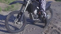 Motocross female rider puts helmet on slow motion upwards pan Stock Footage