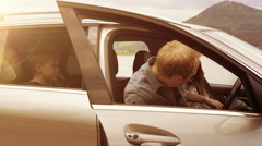 Family with their dog get in a car, fasten their seat-belts and set off Stock Footage