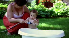 Baby fill the bath in the garden Stock Footage