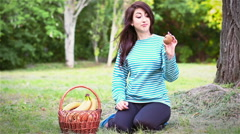 A young girl pulls kiwi from fruit baskets Stock Footage