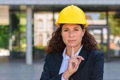 Thoughtful young woman architect wearing a hardhat - stock photo