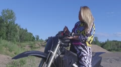 Motocross dirt bike female rider puts her helmet on Stock Footage