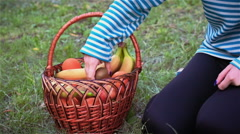 Young girl gets a big kiwi from fruit baskets Stock Footage