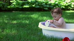 Baby play in the bath outside the house Stock Footage