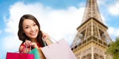 happy woman with shopping bags over eiffel tower - stock photo