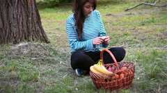 A young girl cleans the orange from the skin near fruit baskets Stock Footage