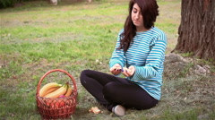 Beautiful girl eating a tangerine near the tree Stock Footage