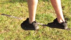 Close up of a tight rope walker feet as he is practicing Stock Footage