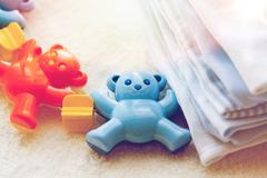 close up of baby rattle and clothes for newborn - stock photo