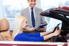 happy woman with car dealer in auto show or salon - stock photo