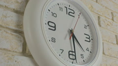 Time four hours thirty minutes. Timelapse. Round white clock hanging on brick - stock footage