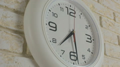 Time seven hours thirty minutes. Timelapse. Round white clock hanging on brick Stock Footage