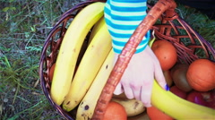 Young woman looking at the basket and searching fruits there Stock Footage