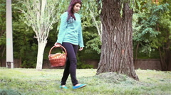 Young woman with fruit basket sits on the grass in the Park Stock Footage