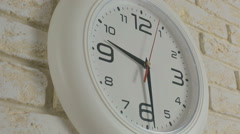 Time nine hours thirty minutes. Timelapse. Round white clock hanging on brick Stock Footage