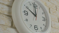 Time ten hours. Timelapse. Round white clock hanging on brick wall Stock Footage