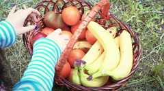 A young woman in sneakers is looking for an orange in a fruit basket Stock Footage