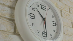 Time ten hours thirty minutes. Timelapse. Round white clock hanging on brick - stock footage