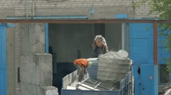 Two men pour cement powder from bucket into bag. Two handymen are working. Stock Footage