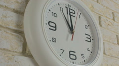 Time eleven hours. Timelapse. Round white clock hanging on brick wall - stock footage