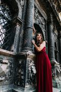 Cheerful young brunette in a red dress posing with old Lviv cathedral on back Stock Photos