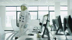 4K Astronaut sitting at desk in room full of computers using touch screen Stock Footage