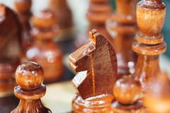 Old Wooden Brown Chess Knight and Pawns Standing On Chessboard - stock photo