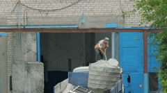 Man mixes cement in a large capacity. A container of cement is in the body truck Stock Footage