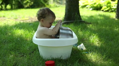 Baby playing with pot in the bath outside Stock Footage